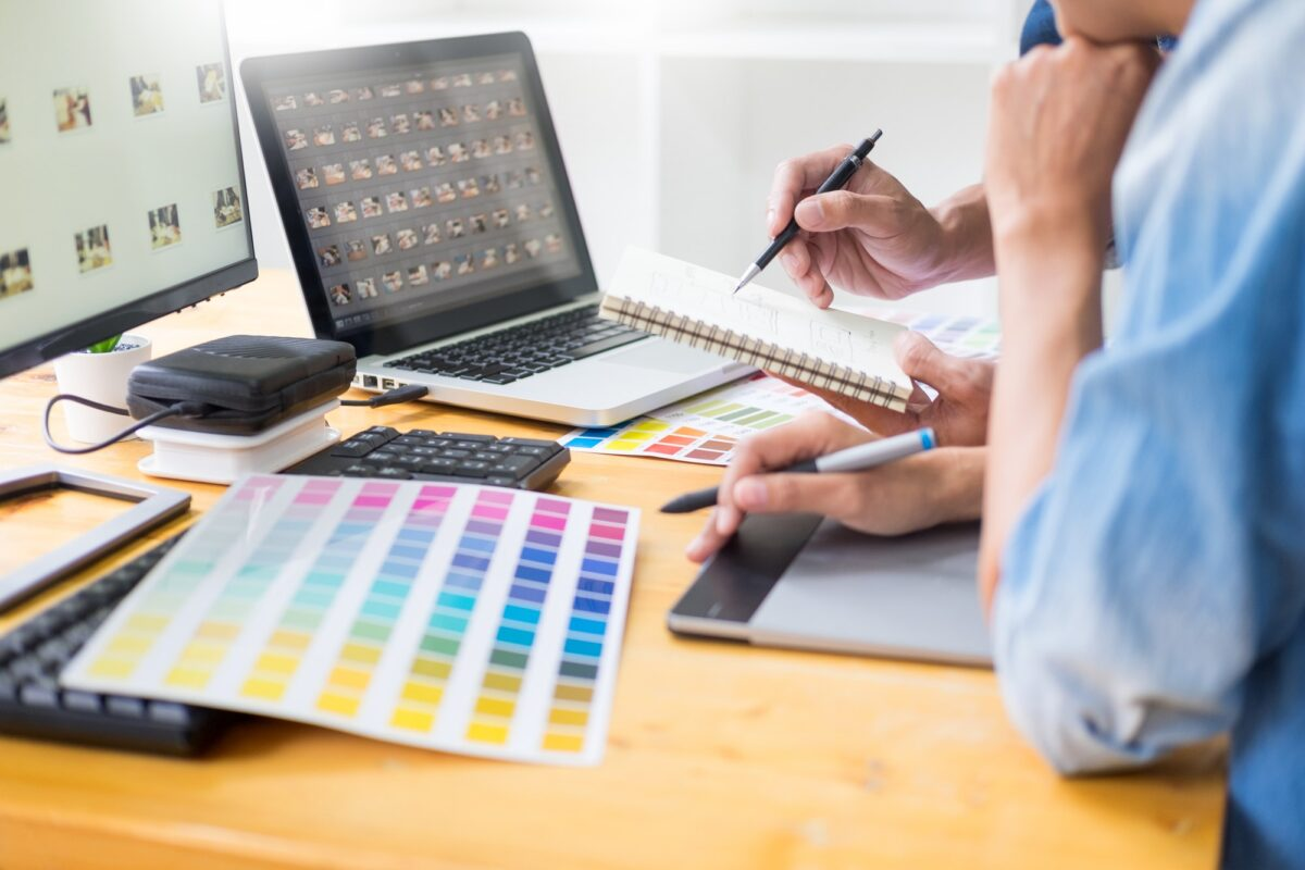 graphic designer team working on web design using color swatches editing artwork using tablet and a